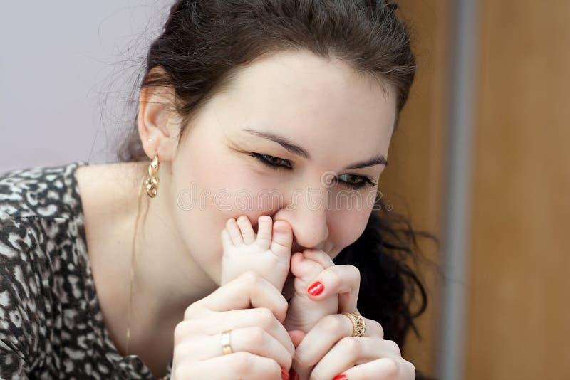 Madre que besa los toies del bebé foto de archivo