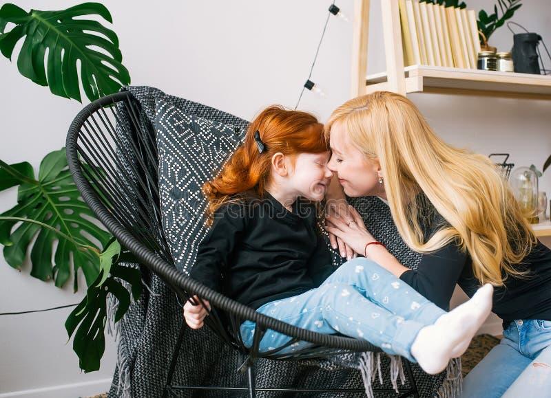 Madre que besa a poca hija del pelirrojo con sentarse en una butaca en un interior casero imagenes de archivo