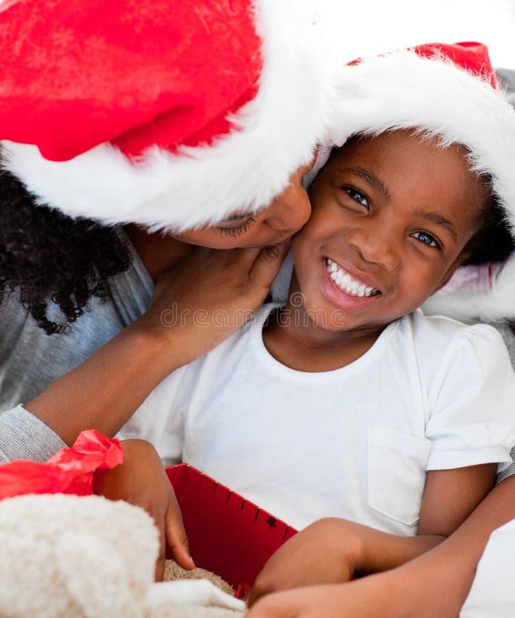 Madre que besa a su hija en la Navidad fotografía de archivo