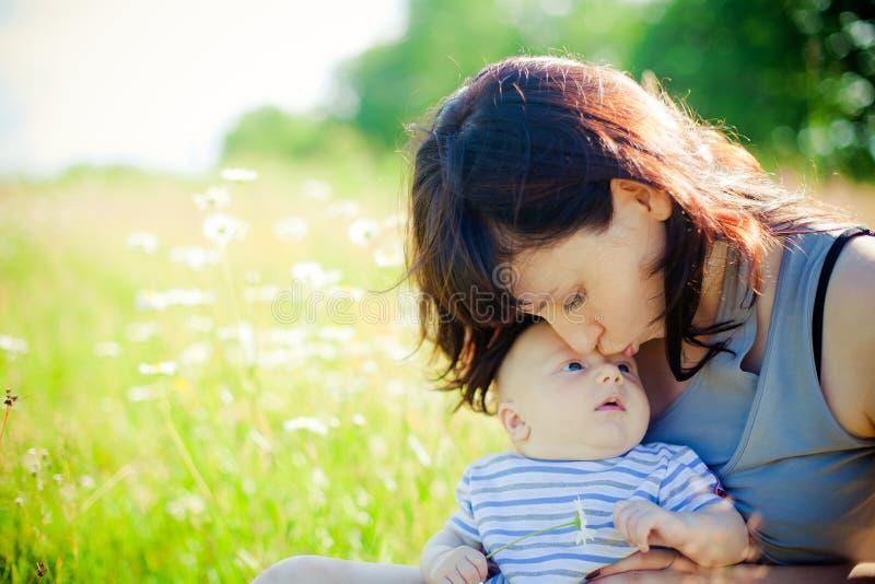 Madre que besa a su pequeño hijo imagen de archivo
