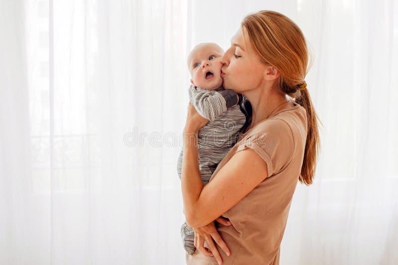 Madre que besa y que abraza al bebé imagen de archivo libre de regalías