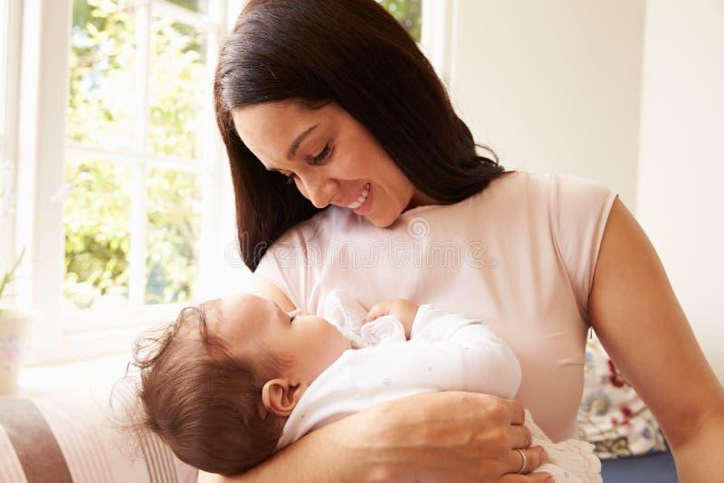 Madre que celebra al bebé durmiente en casa foto de archivo