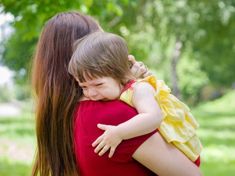 Madre que celebra al bebé gritador con los rasgones foto de archivo