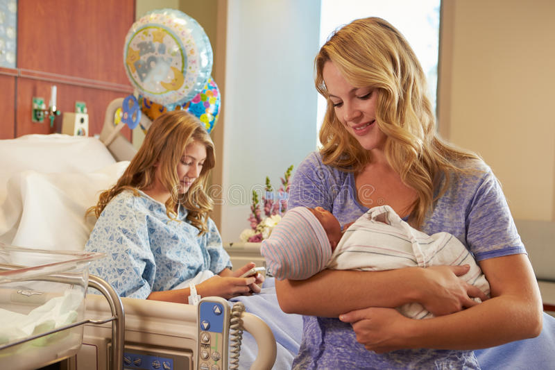 Madre que celebra al bebé recién nacido de la hija adolescente en hospital foto de archivo