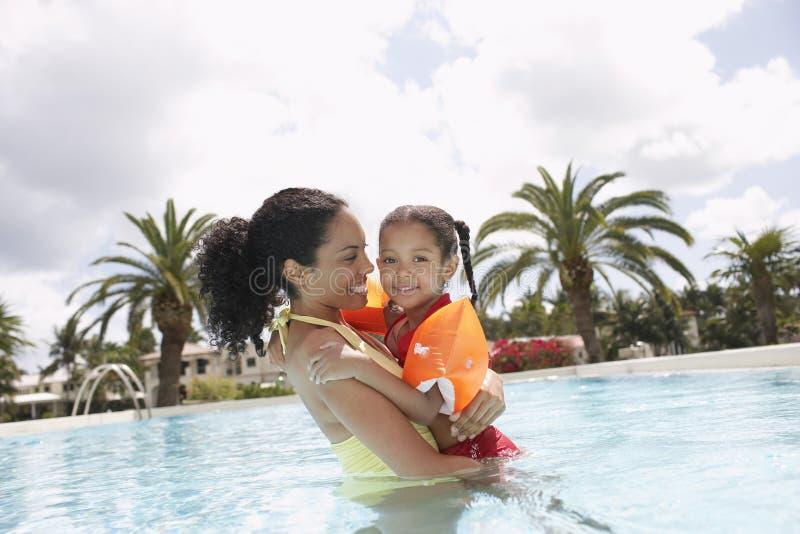 Madre que celebra a la hija en piscina imagen de archivo