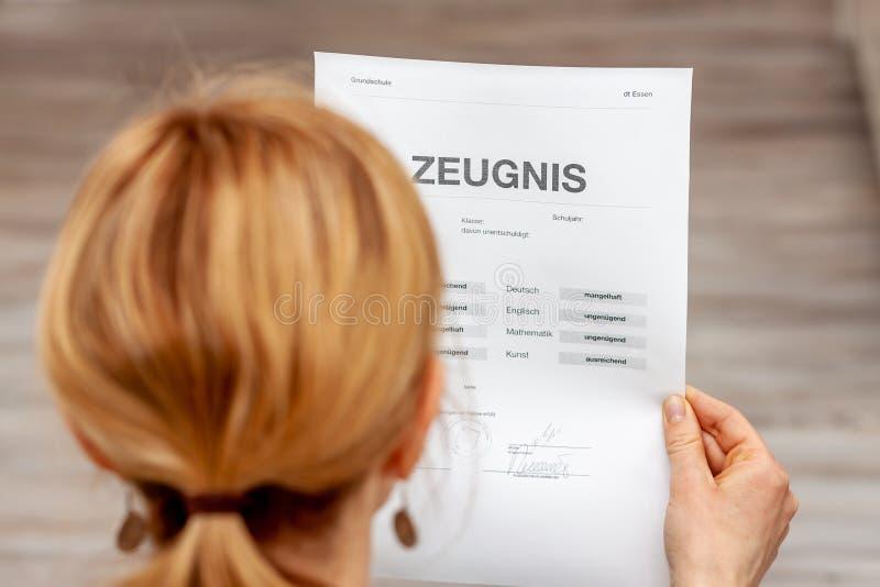 Madre que celebra un certificado alemán muy malo de la escuela en su traducción de las manos: fecha de nacimiento del certificado fotos de archivo