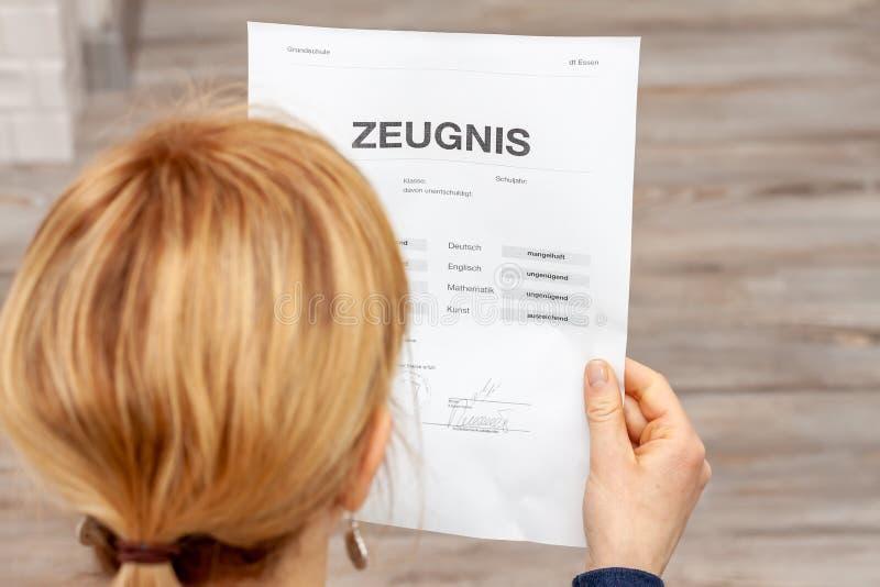 Madre que celebra un certificado alemán muy malo de la escuela en su traducción de las manos: fecha de nacimiento del certificado imagen de archivo libre de regalías