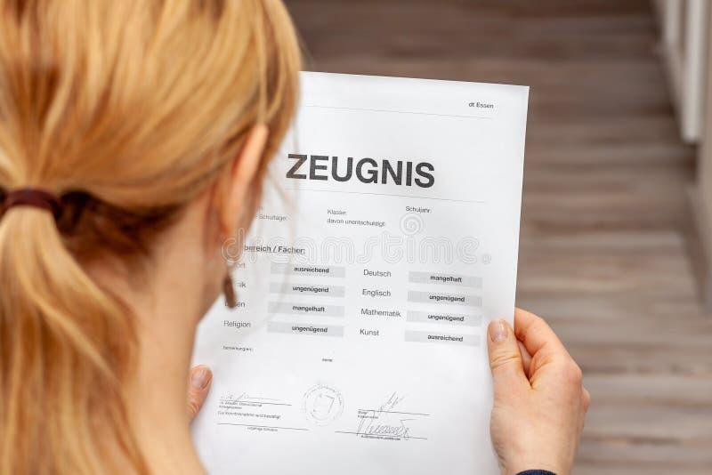 Madre que celebra un certificado alemán muy malo de la escuela en su traducción de las manos: fecha de nacimiento del certificado foto de archivo