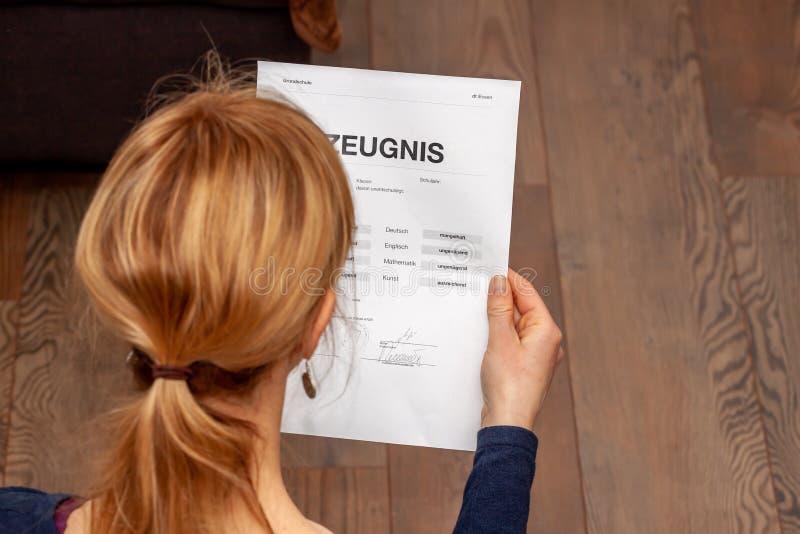 Madre que celebra un certificado alemán muy malo de la escuela en su traducción de las manos: fecha de nacimiento del certificado foto de archivo libre de regalías