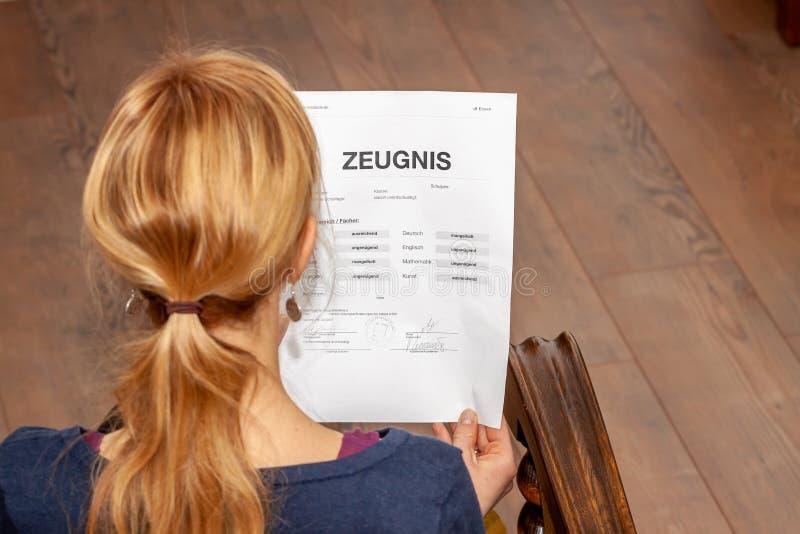 Madre que celebra un certificado alemán muy malo de la escuela en su traducción de las manos: fecha de nacimiento del certificado imágenes de archivo libres de regalías
