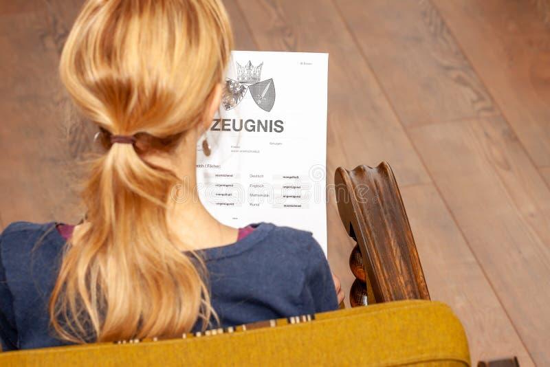 Madre que celebra un certificado alemán muy malo de la escuela en su traducción de las manos: fecha de nacimiento del certificado imagenes de archivo
