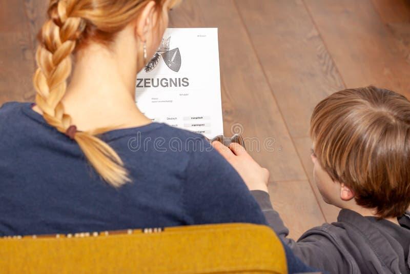 Madre que celebra un certificado alemán muy malo de la escuela en su traducción de las manos: fecha de nacimiento del certificado imagen de archivo