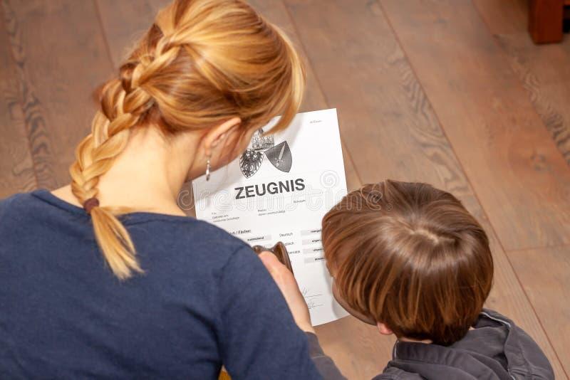 Madre que celebra un certificado alemán muy malo de la escuela en su traducción de las manos: fecha de nacimiento del certificado fotografía de archivo libre de regalías