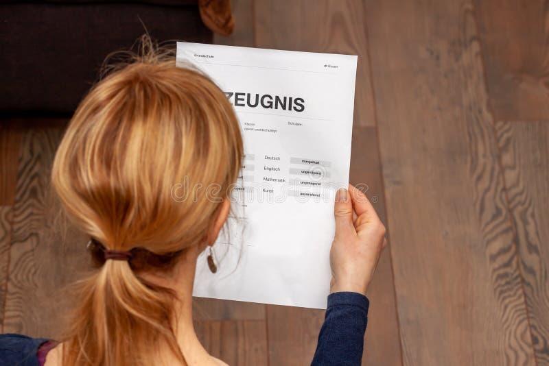 Madre que celebra un certificado alem?n muy malo de la escuela en su traducci?n de las manos: fecha de nacimiento del certificado foto de archivo