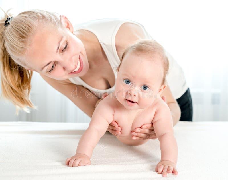 Madre que celebra y que juega con recién nacido en casa foto de archivo