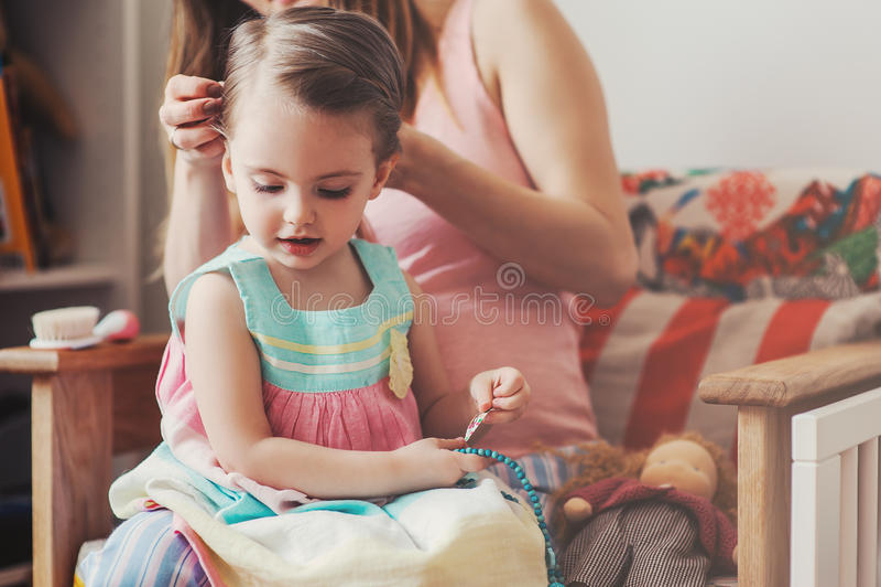 Madre que cepilla su pelo de la hija del bebé en casa foto de archivo libre de regalías