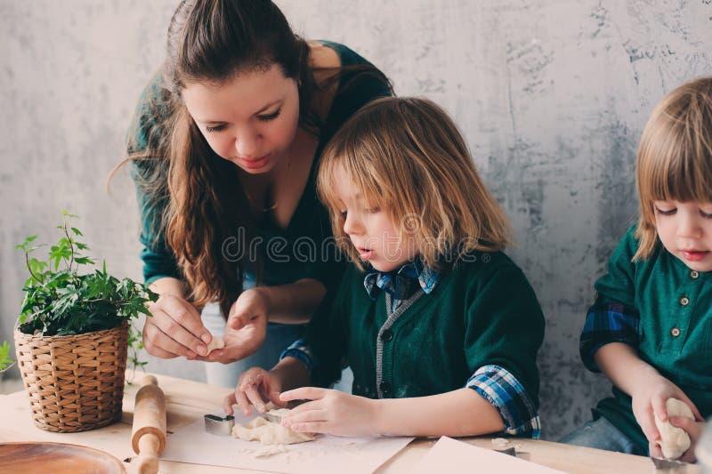 Madre que cocina con los niños en cocina Hermanos del niño que cuecen junto y que juegan con los pasteles en casa imagen de archivo libre de regalías
