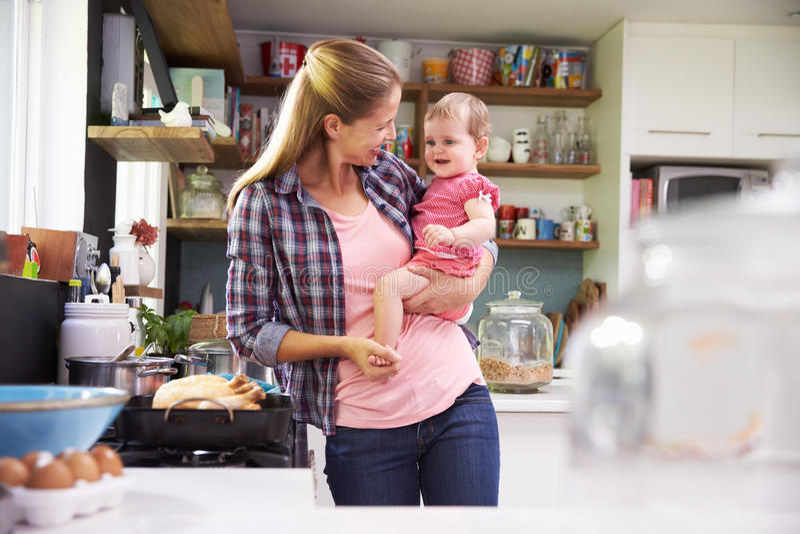 Madre que cocina la comida mientras que detiene a la hija en cocina imagen de archivo