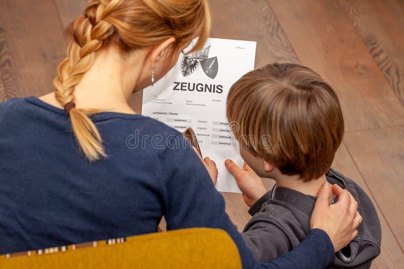 Madre que conforta al hijo a pesar del mún certificado de la escuela - traducción: fecha de nacimiento del certificado la música  foto de archivo