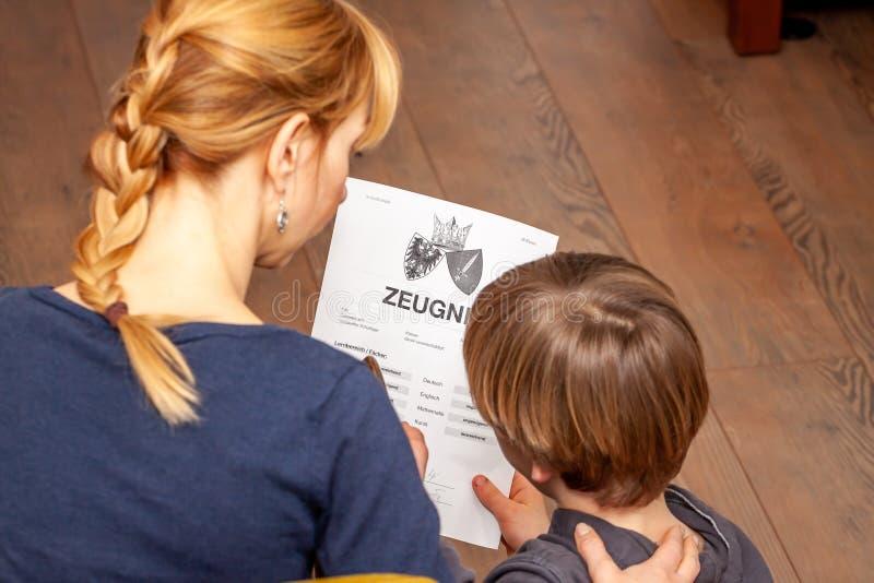 Madre que conforta al hijo a pesar del mún certificado de la escuela - traducción: fecha de nacimiento del certificado la música  imagen de archivo