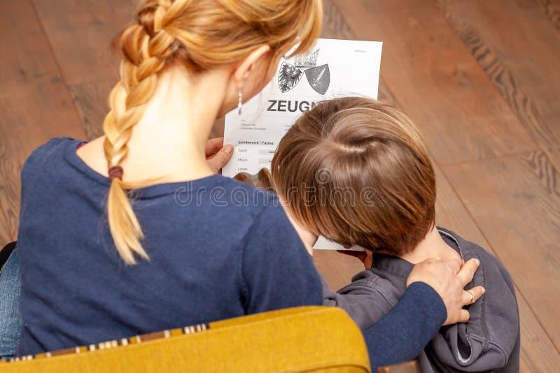Madre que conforta al hijo a pesar del mún certificado de la escuela - traducción: fecha de nacimiento del certificado la música  fotos de archivo libres de regalías