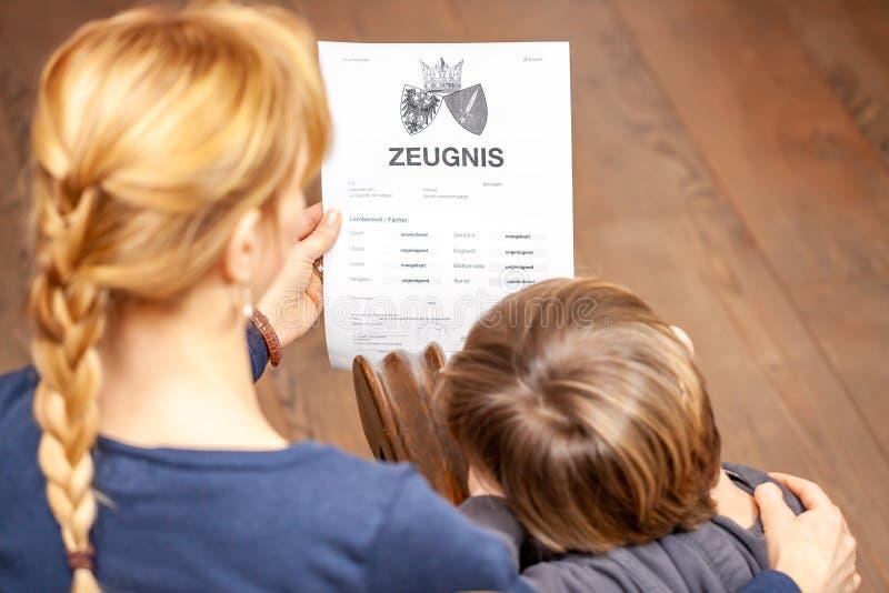 Madre que conforta al hijo a pesar del mún certificado de la escuela - traducción: fecha de nacimiento del certificado la música  imágenes de archivo libres de regalías