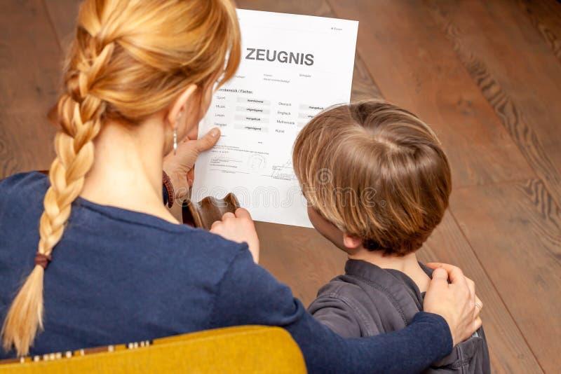 Madre que conforta al hijo a pesar del mún certificado de la escuela - traducción: fecha de nacimiento del certificado la música  imagen de archivo libre de regalías