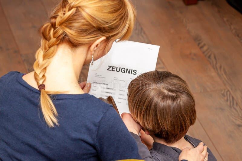 Madre que conforta al hijo a pesar del m?n certificado de la escuela - traducci?n: fecha de nacimiento del certificado la m?sica  imágenes de archivo libres de regalías