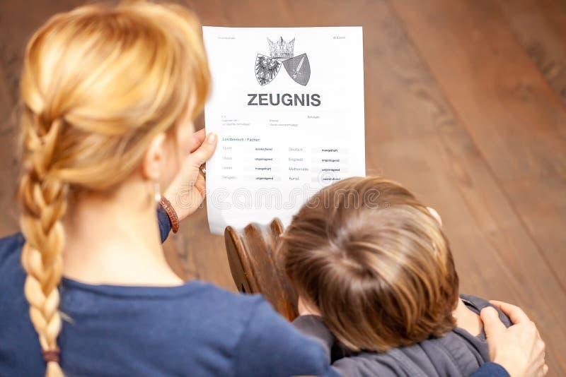 Madre que conforta al hijo a pesar del m?n certificado de la escuela - traducci?n: fecha de nacimiento del certificado la m?sica  fotos de archivo