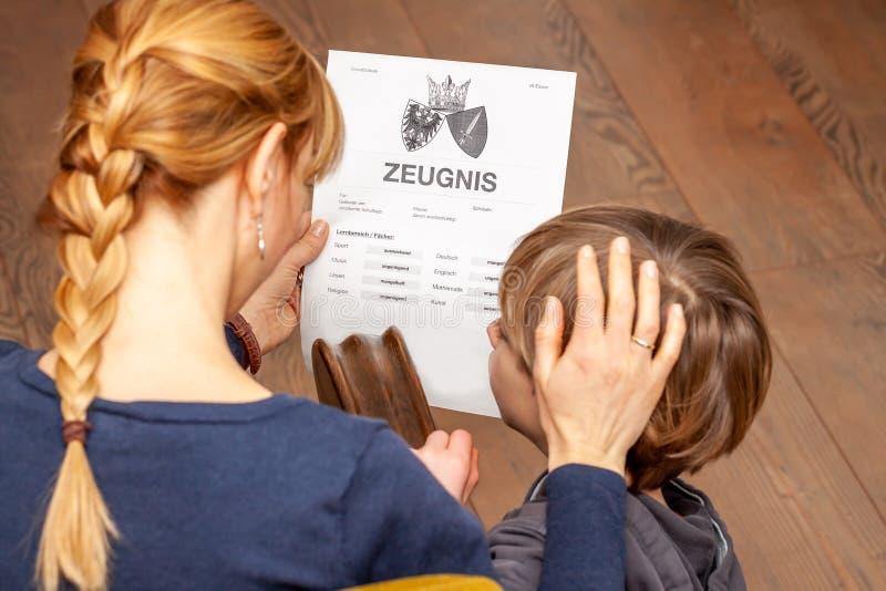 Madre que conforta al hijo a pesar del m?n certificado de la escuela - traducci?n: fecha de nacimiento del certificado la m?sica  imagen de archivo