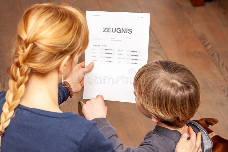 Madre que conforta al hijo a pesar del m?n certificado de la escuela - traducci?n: fecha de nacimiento del certificado la m?sica  imagen de archivo libre de regalías