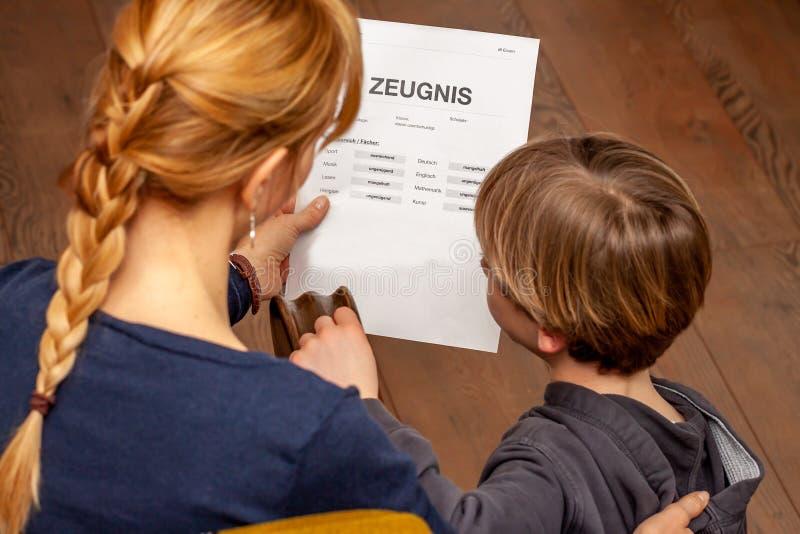 Madre que conforta al hijo a pesar del m?n certificado de la escuela - traducci?n: fecha de nacimiento del certificado la m?sica  fotografía de archivo