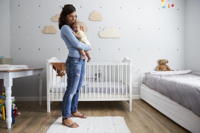 Madre que conforta al hijo recién nacido del bebé en cuarto de niños foto de archivo libre de regalías