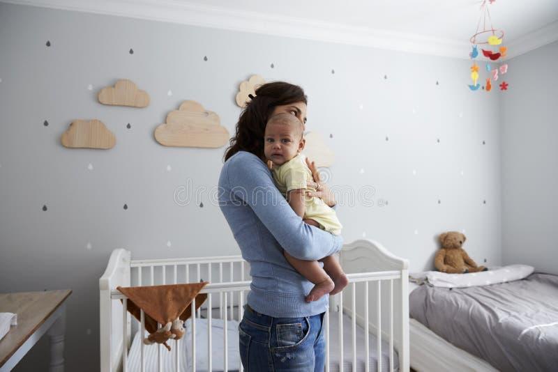 Madre que conforta al hijo recién nacido del bebé en cuarto de niños imagen de archivo libre de regalías
