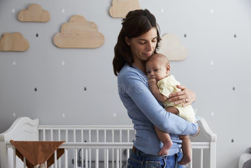 Madre que conforta al hijo recién nacido del bebé en cuarto de niños fotos de archivo libres de regalías