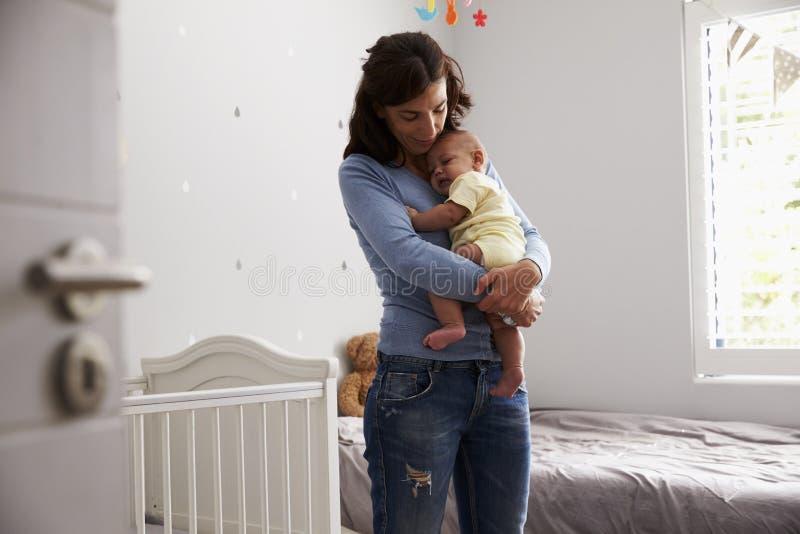 Madre que conforta al hijo recién nacido del bebé en cuarto de niños fotos de archivo
