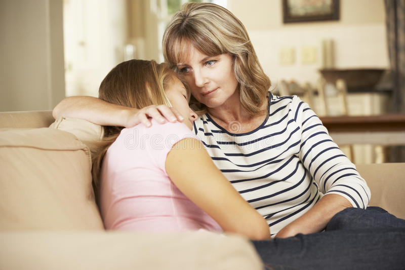 Madre que conforta a la hija adolescente que se sienta en Sofa At Home foto de archivo libre de regalías