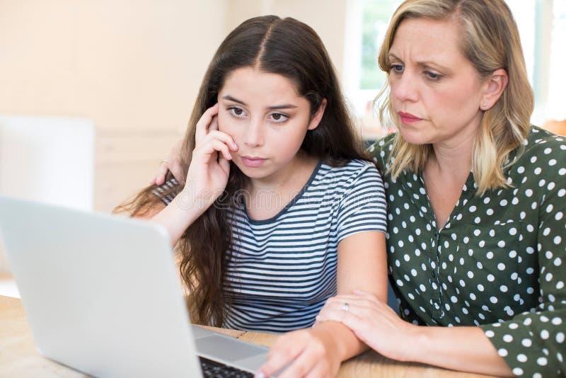 Madre que conforta a la hija discriminada en línea tiranizando foto de archivo