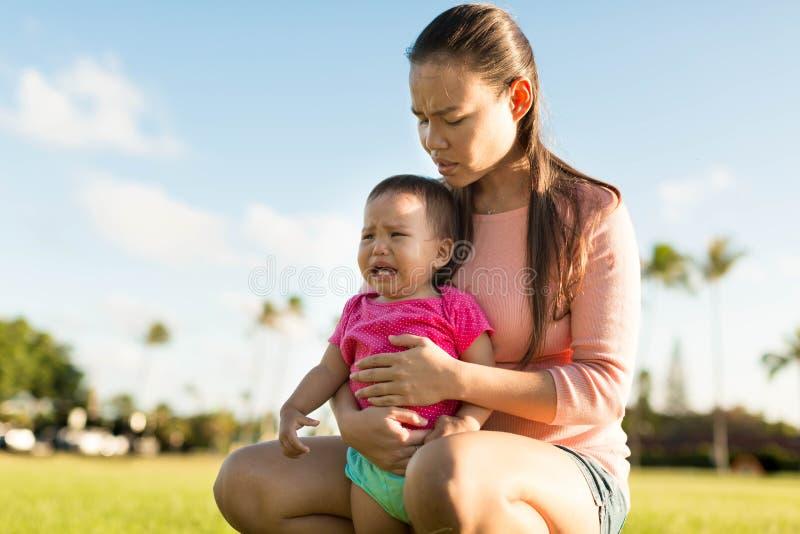 Madre que conforta a su hija joven del trastorno imagenes de archivo