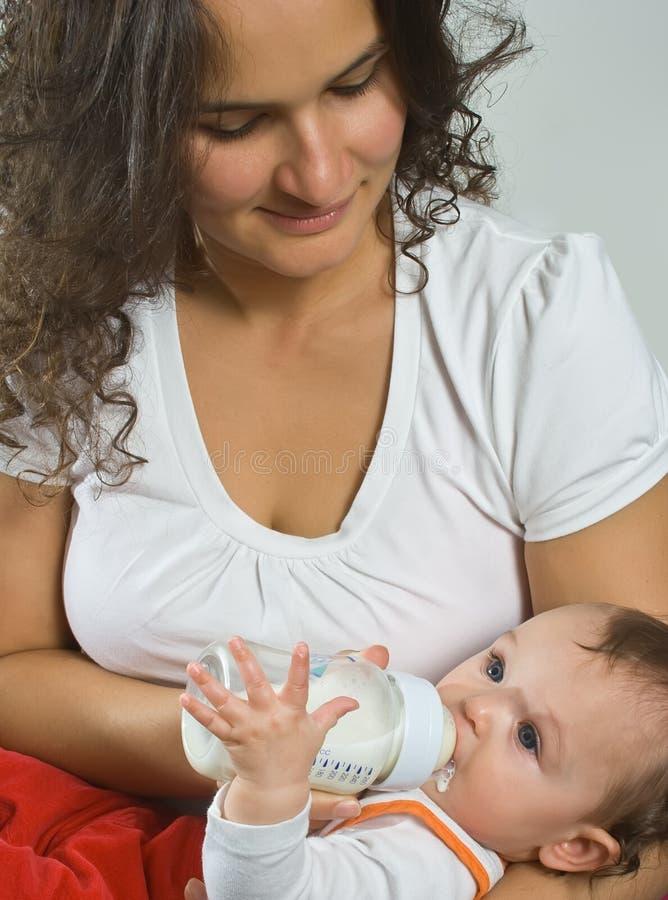Madre que cría con biberón al bebé fotografía de archivo libre de regalías