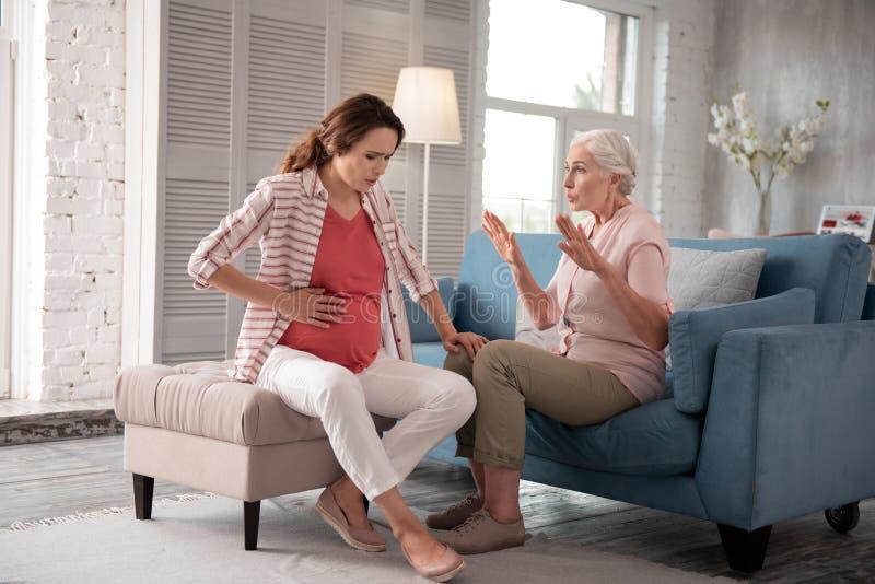 Madre que cuida que calma a su hija embarazada que tiene dolor imagen de archivo