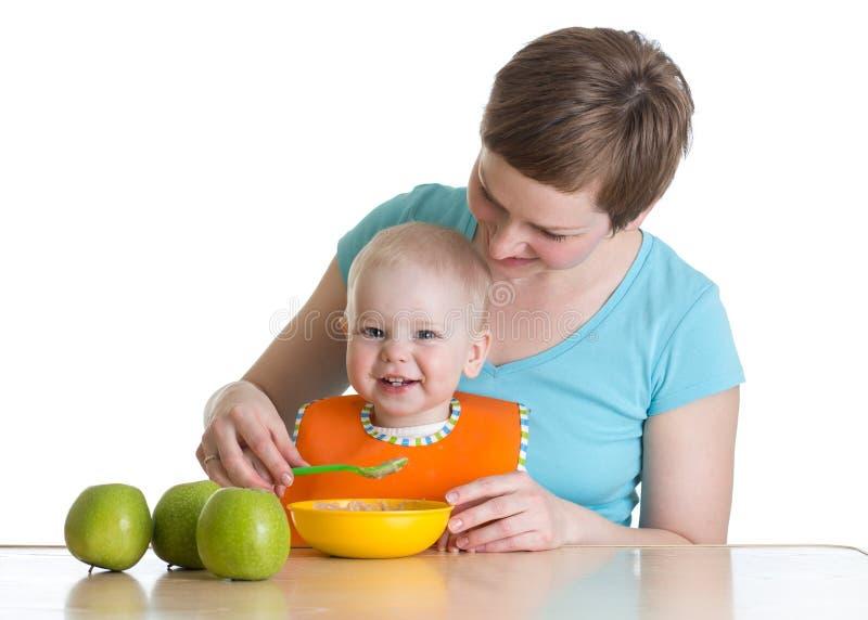 Madre que da de comer a la boca a su bebé aislado en blanco imagen de archivo libre de regalías