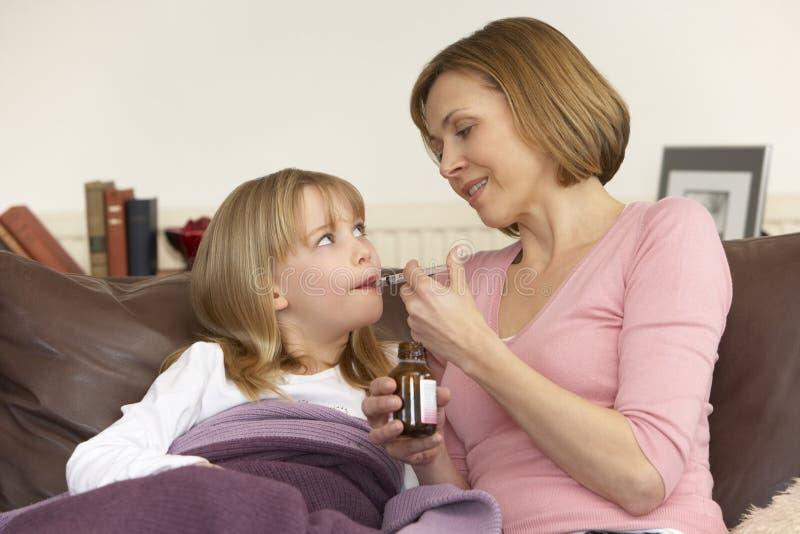 Madre que da la medicina a la hija enferma imagen de archivo libre de regalías