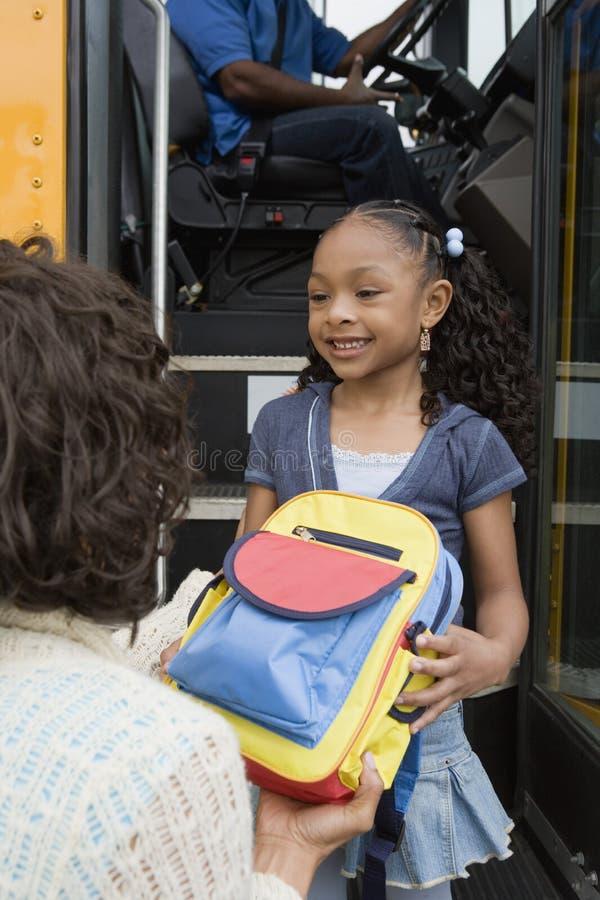 Madre que da la mochila de la hija en el autobús escolar fotos de archivo libres de regalías