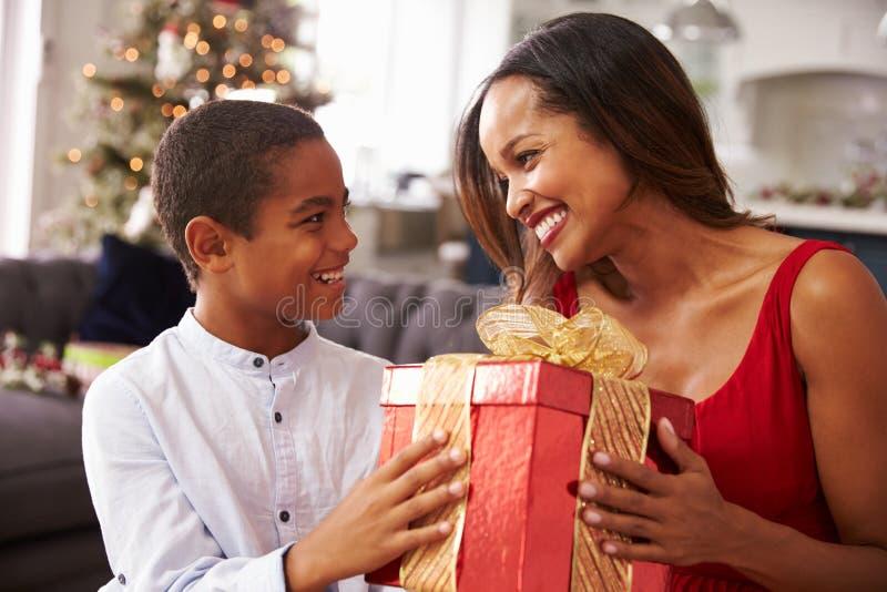 Madre que da regalos de Navidad al hijo en casa imágenes de archivo libres de regalías