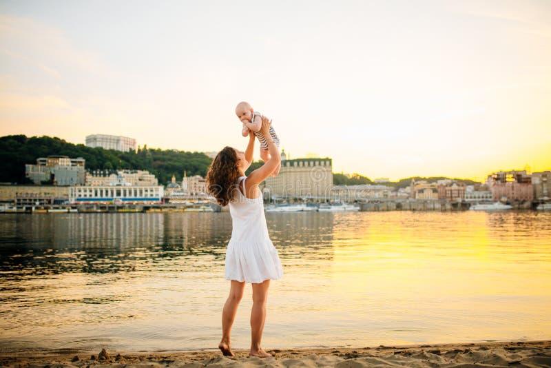 Madre que da vuelta al niño contra una puesta del sol y un agua Mama y beb? felices El jugar en la playa Mujer joven que lanza en foto de archivo libre de regalías