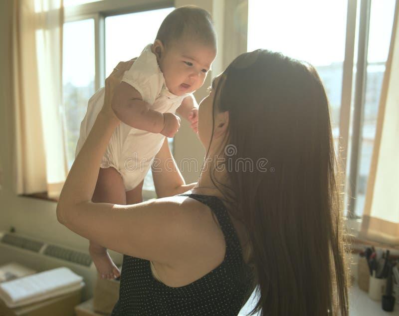 Madre que detiene a su bebé con amor fotografía de archivo