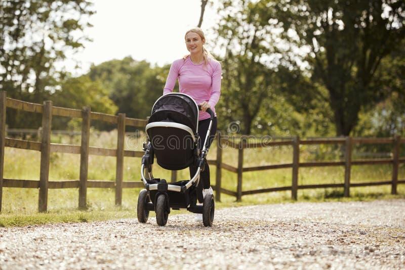 Madre que ejercita corriendo mientras que empuja el cochecillo de bebé imágenes de archivo libres de regalías