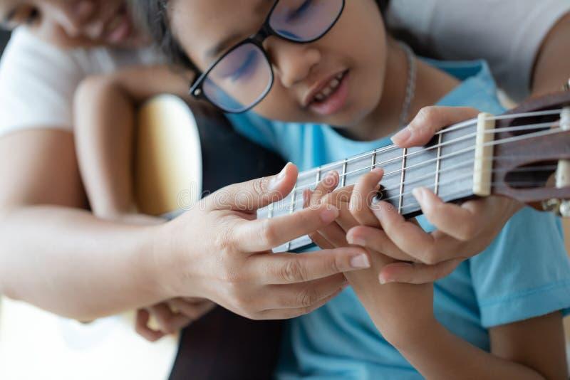 Madre que enseña a la hija que aprende cómo tocar la guitarra clásica acústica para el jazz y el foco selecto fácil de la canción imagen de archivo