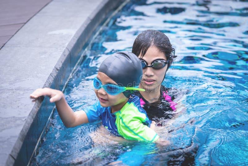 Madre que enseña a su hijo a nadar fotos de archivo